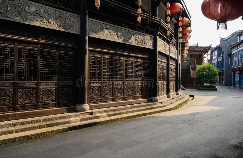 Skuggig stenhäll-stenlagd gata mellan traditionella byggnader i su arkivbild