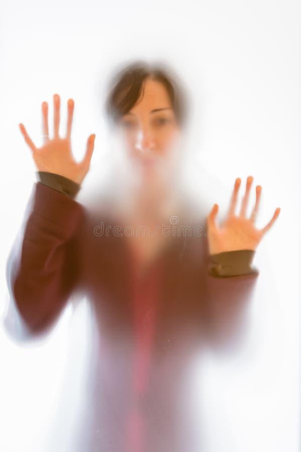 Skuggigt kvinnadiagram bak ett frostat exponeringsglas royaltyfri fotografi