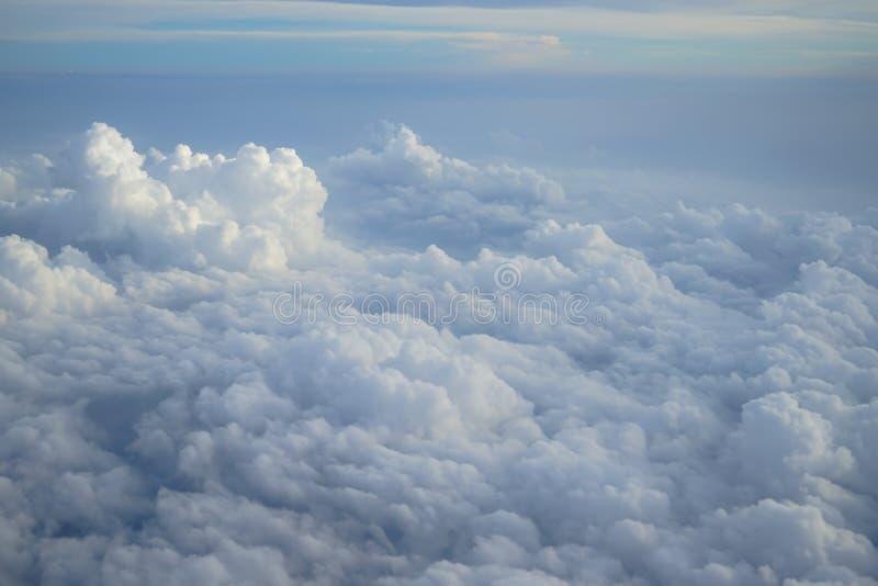 Skuggor av ljus - blå himmel och ständigt ändring för färg som svävar den vita cloudscapesikten från flygplanfönster royaltyfri bild