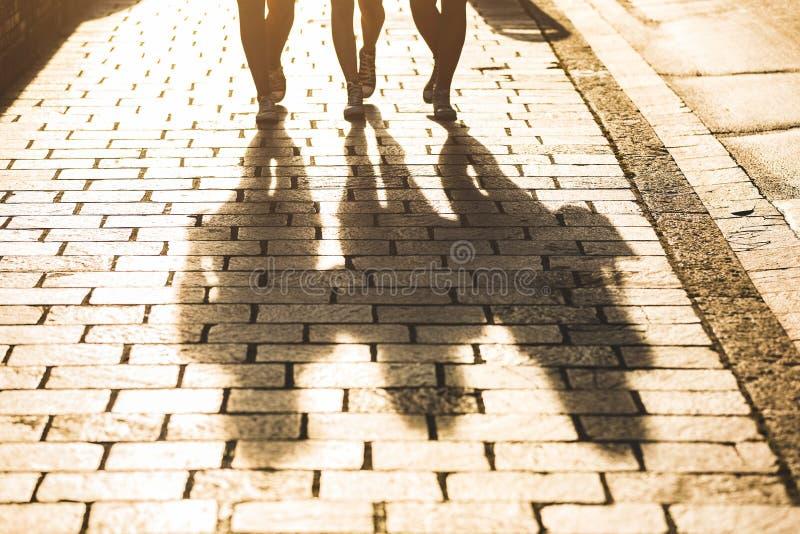 Skuggor av tre flickor som går på en trottoar i staden arkivfoto