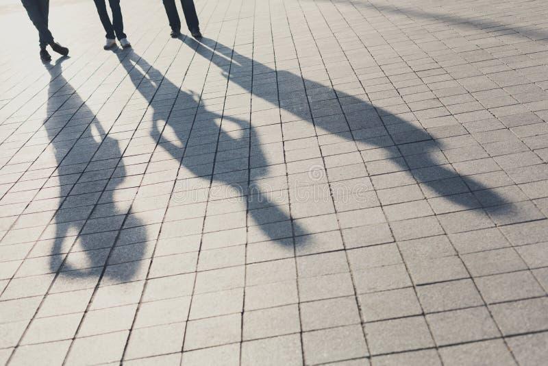 Skuggor av tre vänner på trottoar arkivfoto