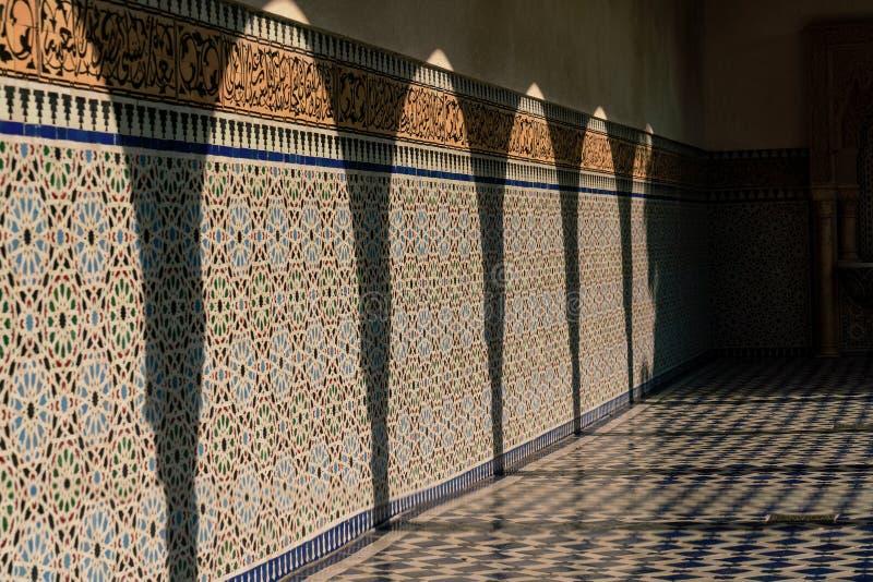 Skuggor på en solig orientalisk stil belagd med tegel vägg arkivbild
