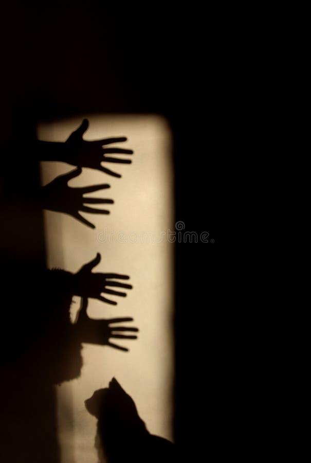 Skuggor vid händer på väggen royaltyfri fotografi