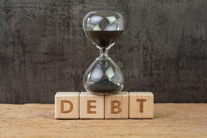 Skuld, finansiellt åtagande som kör för bristningsnedräkning för ekonomisk bubbla begrepp, sandglass eller timglas på träkubkvart arkivbild
