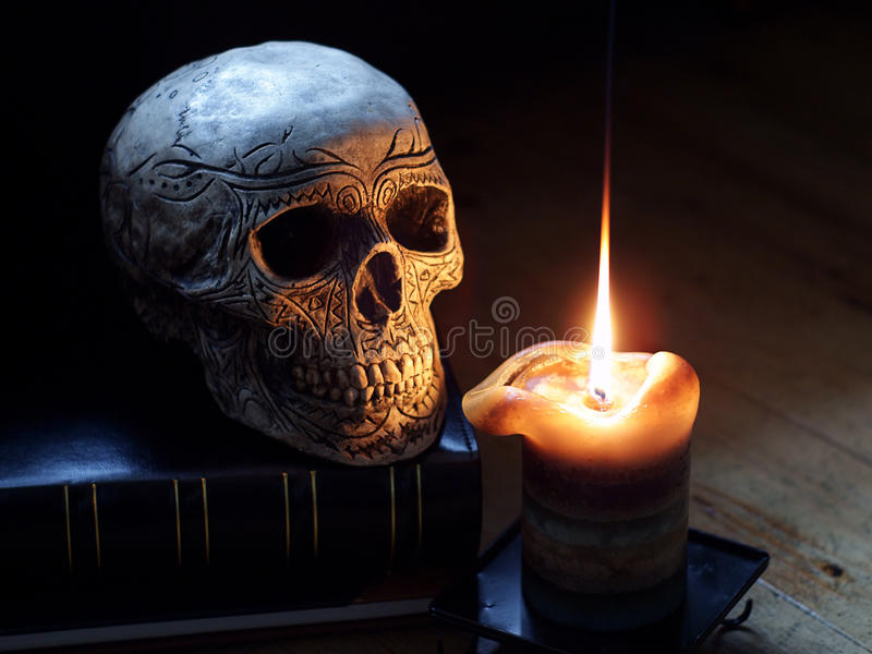 Skull and Candle. A still life horror or halloween shot of an ornamental decorated skull and a lit candle royalty free stock photography