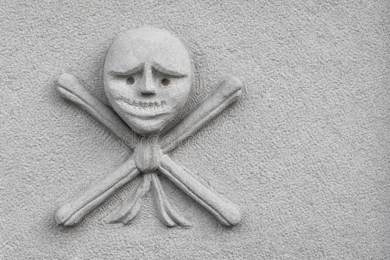 Skull and crossed bones carved on an new stone royalty free stock photography
