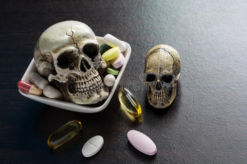 Skull and diferent Tablets pills capsule heap mix therapy drugs. Doctor flu antibiotic pharmacy medicine medical on dark background - Concept of a drug overdose stock photo