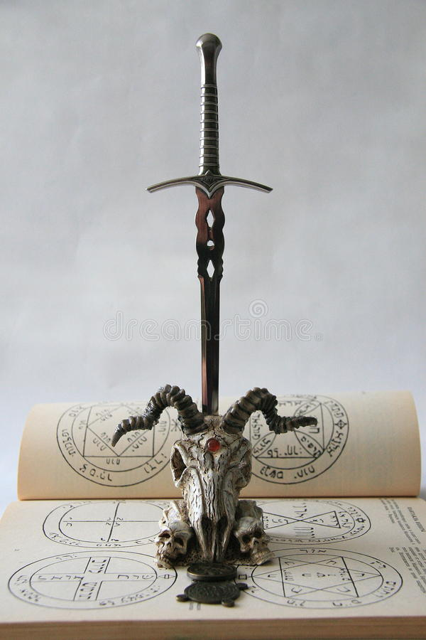 Skull with a knife and pentagram stock photo