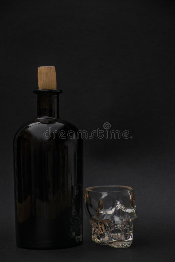 Bottle of strong alcohol with a glass glass on a black background stock photos