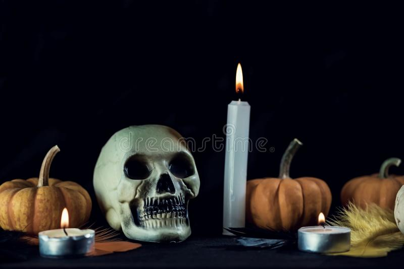 Skull, pumpkin and candles on a black background for a halloween decoration, close up royalty free stock photo