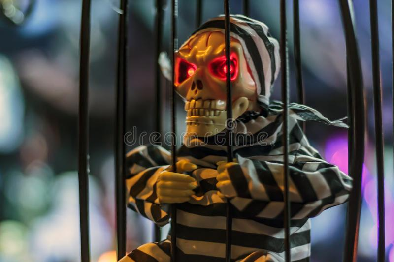 Skull with red eyes in a cage. Halloween concept royalty free stock images