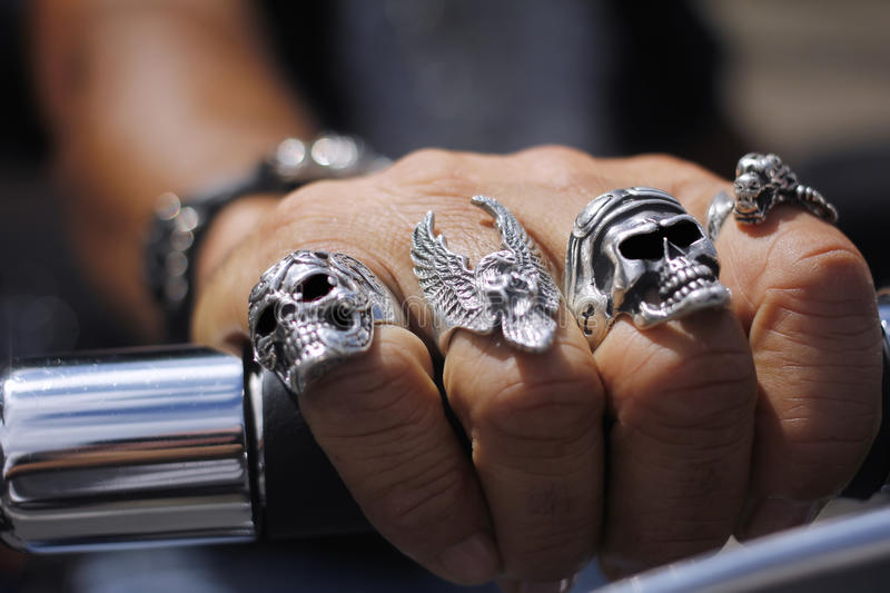 Skull rings on hand. Skull rings on fingers of hand gripping motorcycle handlebar royalty free stock photos