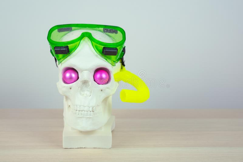 Skull sculpture with pink eyes in a snorkeling green mask and yellow tube.  royalty free stock photos