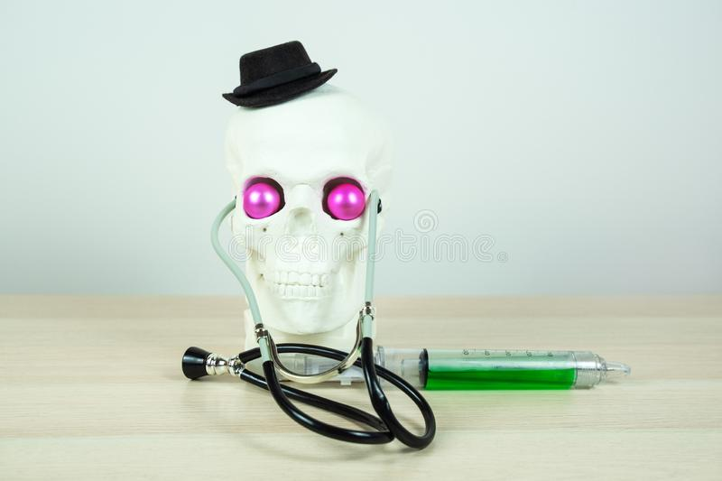 Skull sculpture wearing black elegant hat, stratoscopes, with big medical syringe and bright pink eyes. parody of a medical worker stock images