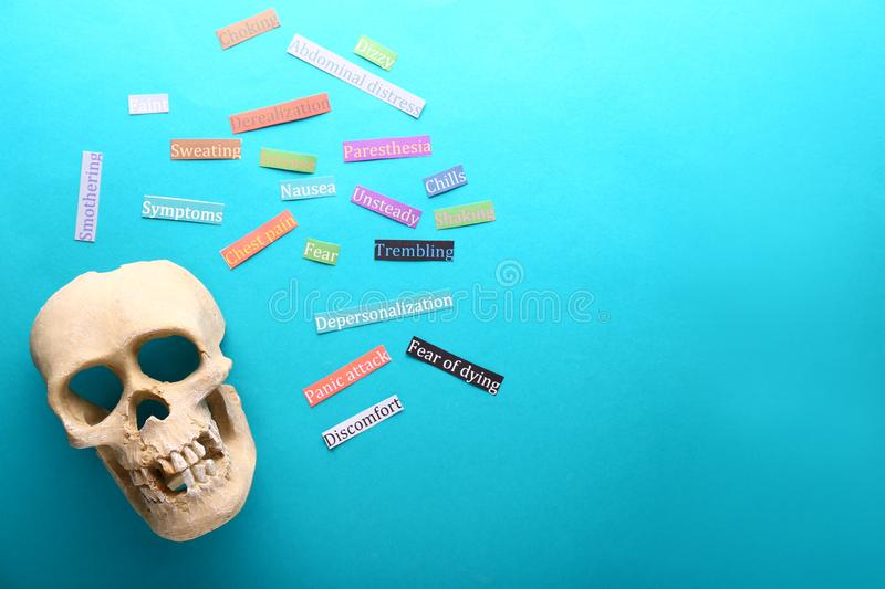 Skull and stickers with symptoms of panic attack on color background, flat lay royalty free stock photos