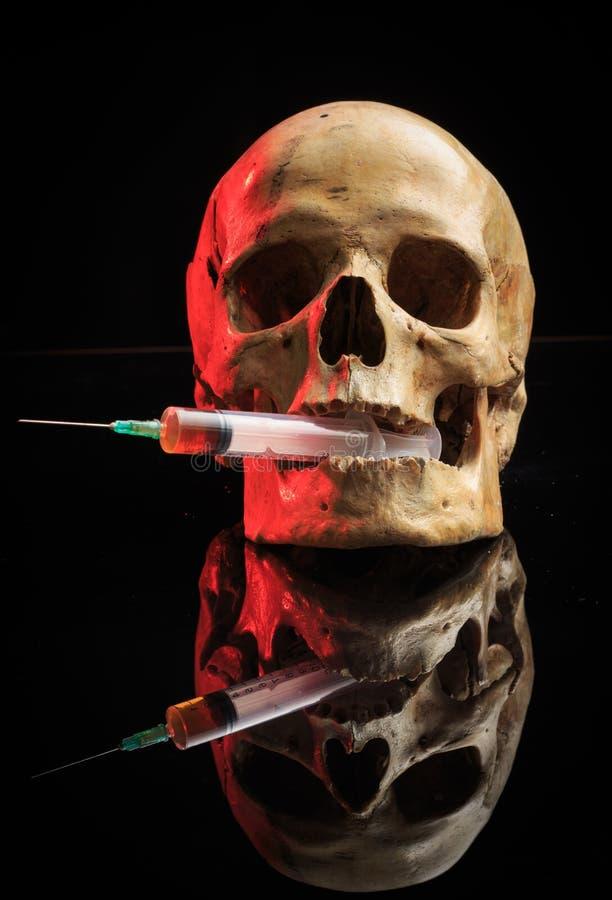 Skull and syringe of yellowish liquid. concept royalty free stock photo