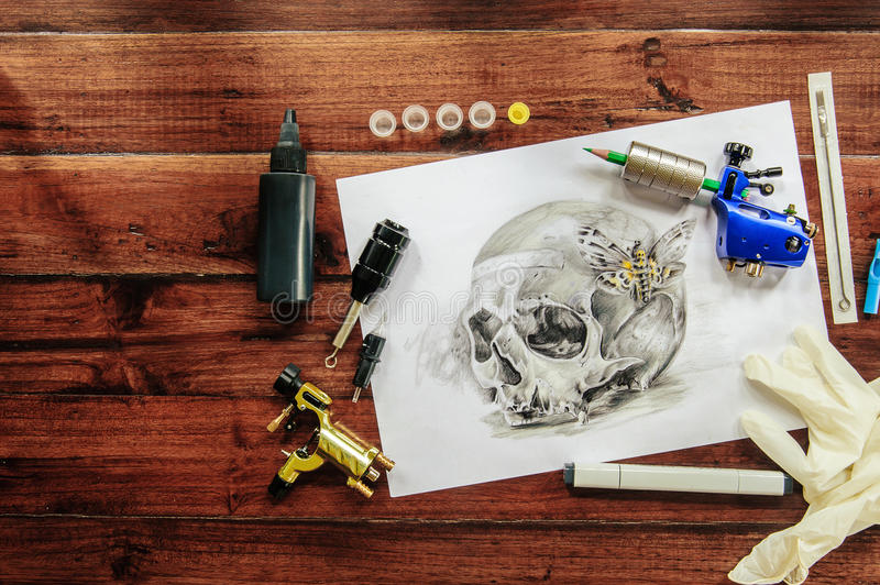 Skull tattoo sketch with rotary machines. Needles, grips and gloves on wooden background royalty free stock photo