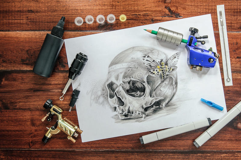 Skull tattoo sketch with rotary machines. Needles, grips on wooden background stock photography