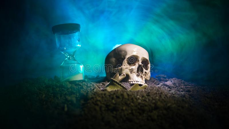 Skull and vintage hourglass on dark toned foggy background under beam of light. Horror concept. royalty free stock images