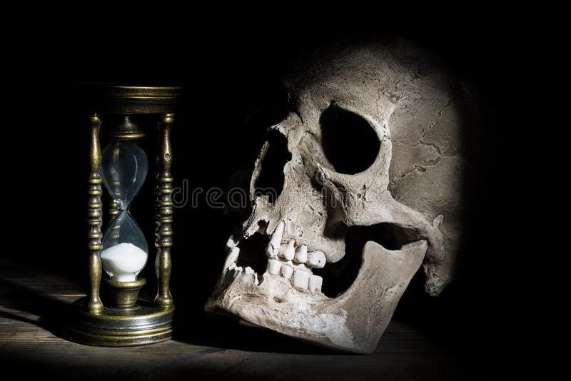 Skull and vintage hourglass on wooden background under beam of light stock photography