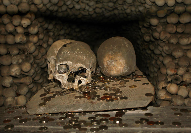 Skulls and coins in ossuary stock image