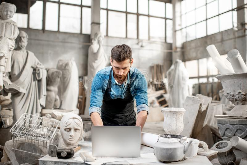 Skulptör som arbetar med bärbara datorn i studion royaltyfria bilder