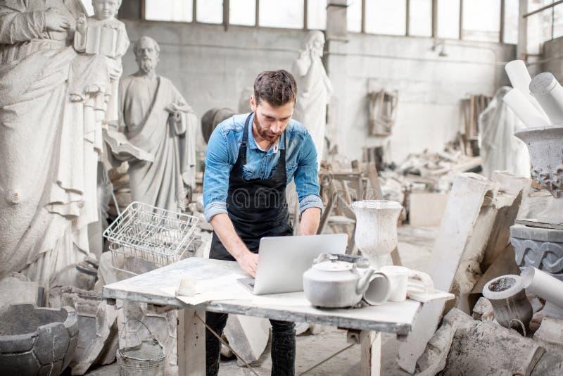 Skulptör som arbetar med bärbara datorn i studion arkivbilder