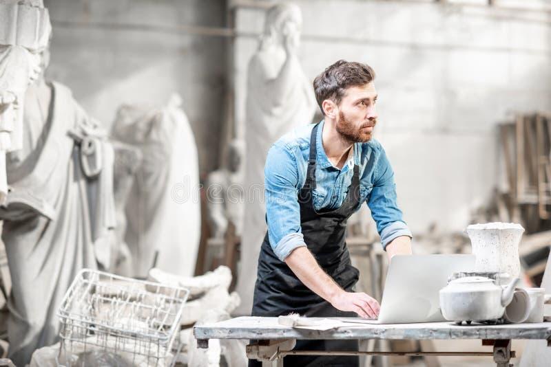 Skulptör som arbetar med bärbara datorn i studion arkivbild