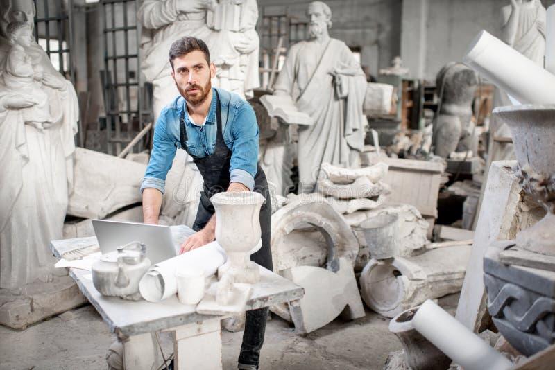 Skulptör som arbetar med bärbara datorn i studion royaltyfri bild