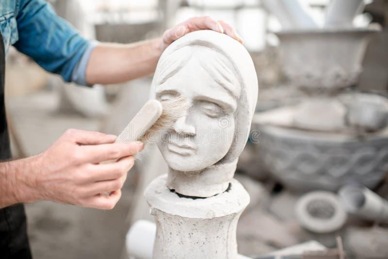 Skulptör som arbetar med skulptur i studion arkivfoton
