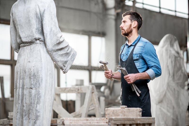 Skulptör som arbetar med skulpturer i studion arkivbild