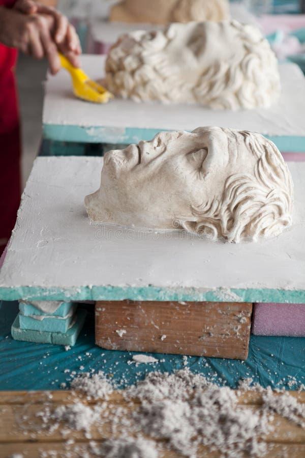 Skulptör som arbetar på head skulptur arkivbild