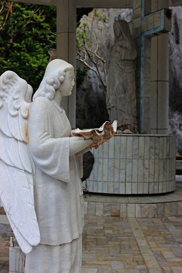 Skulptur av en ängel med ett havsskal philippines arkivbilder