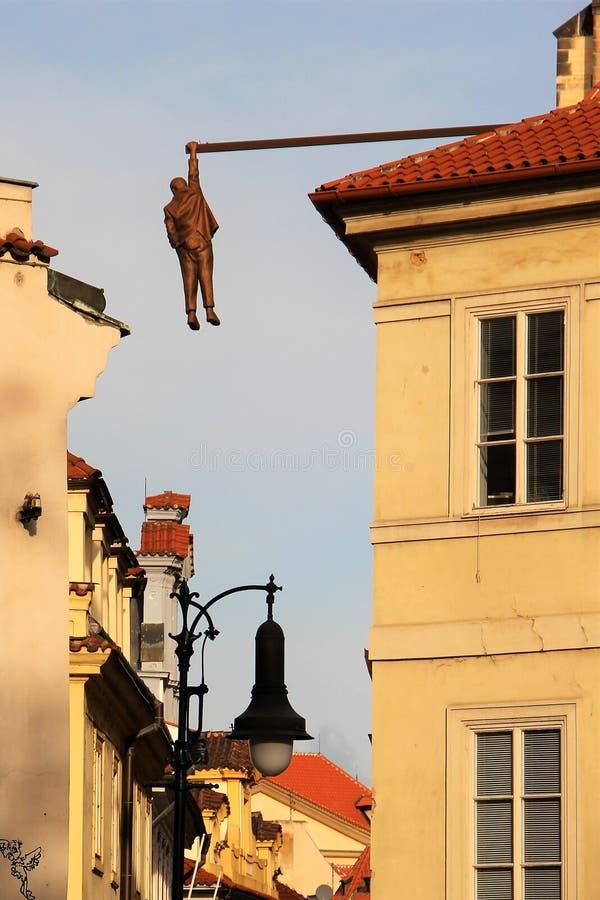 Skulptur av en hängande man i en smal gammal gata i mitten av Prague, Tjeckien arkivbilder