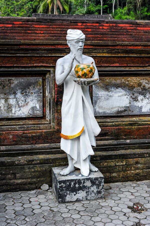 Skulptur av en hinduisk präst som rymmer en kopp av heligt vatten i Tirta royaltyfri foto