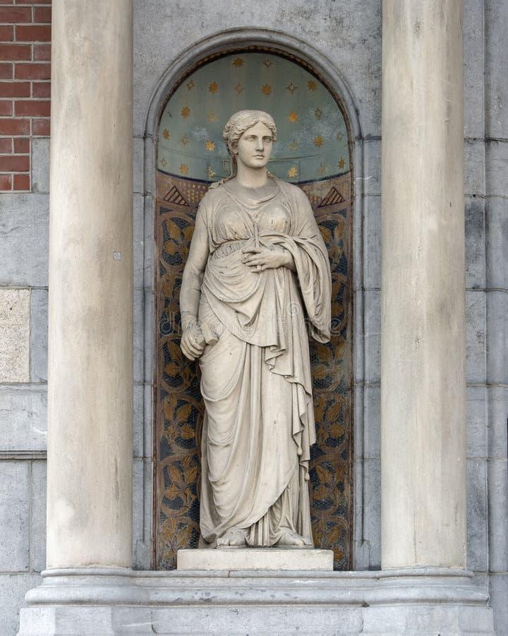 Skulptur av en kvinna i ett skepp mellan två kolonner, bredvid ingången till Rijksmuseumen, Amsterdam royaltyfri bild