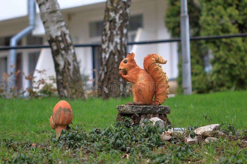 Skulptur av en röd ekorre på en stubbe royaltyfria foton