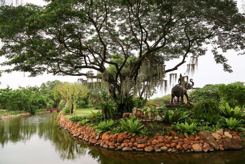 Skulptur av en ryttare på en elefant nära ett träd på banken av t arkivfoton