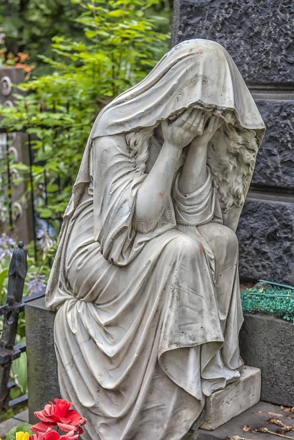 Skulptur av en sörja kvinna på en grav royaltyfri foto