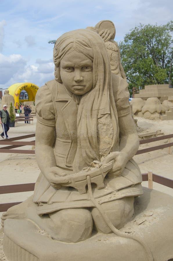 Skulptur av ett barn som spelar en videospel i sandskulpturfestival i Lappeenranta arkivbilder