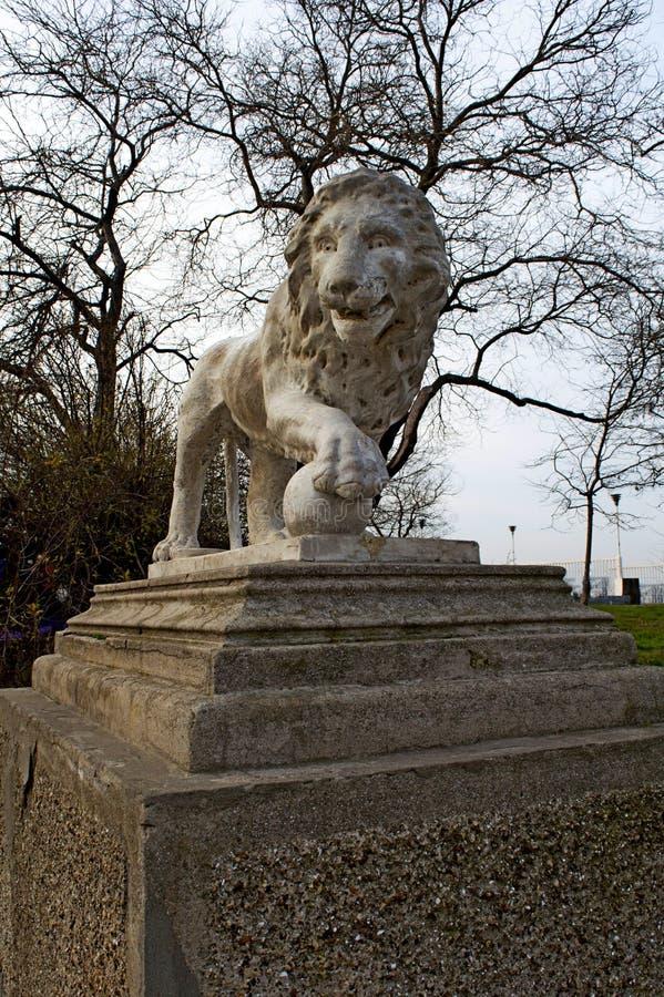 Skulptur av ett lejon på en sockel i en parkera royaltyfri foto