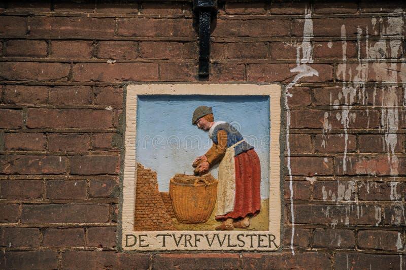 """Skulptur av kvinnaarbete, var är skriftlig """"deturfvulster"""" i holländare som är den betyder  för """"thetorvfiller†i Amsterd royaltyfri bild"""