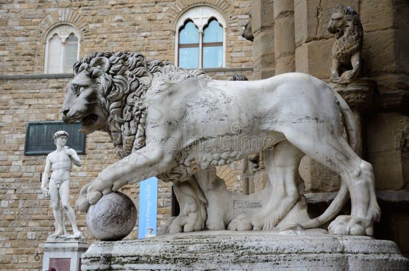 Skulptur av Medici lejon och kopia av Michelangelos den David statyn royaltyfria bilder