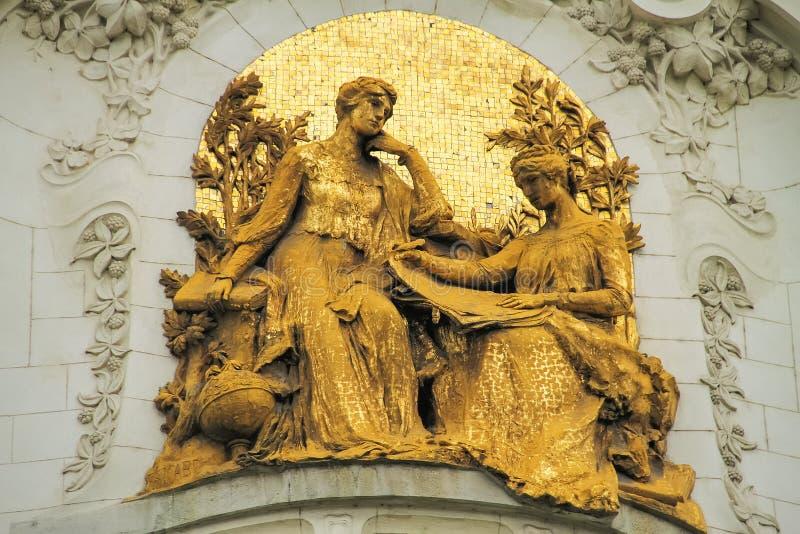 Skulptur av två kvinnor i guld på byggnaden arkivfoto