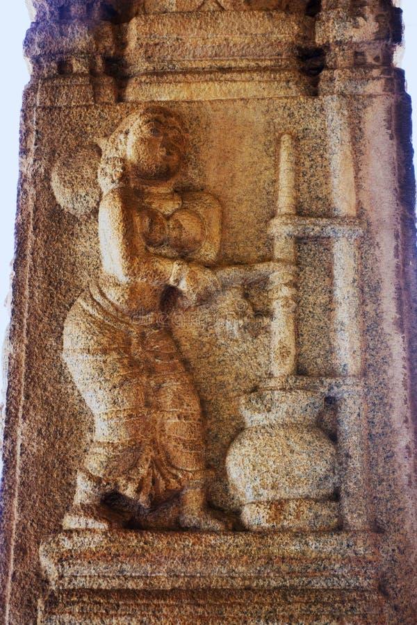 Skulptur av Yashoda som gör ostmassa på den Vittala templet, Hampi, Karnataka, Indien arkivfoton