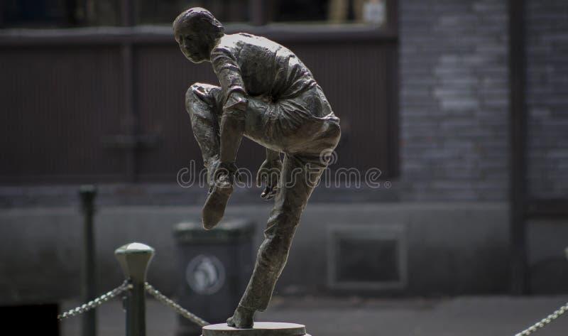 Skulptur einer Frau, die auf einen Schuh sich setzt stockbild