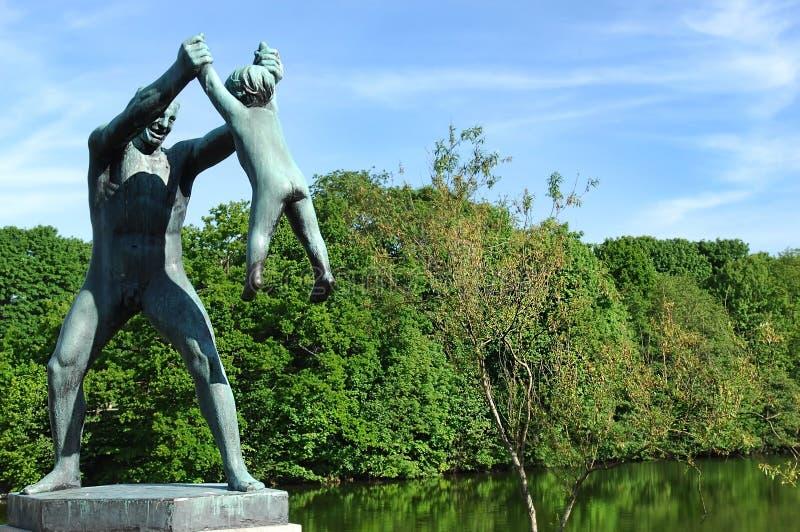 Skulptur eines Mannes, der mit einem Kind spielt stockfotos