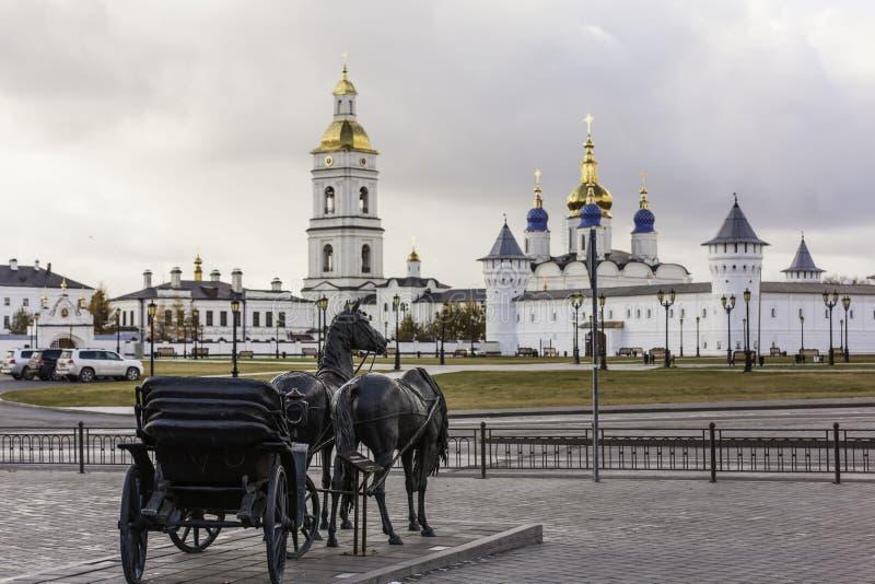 Skulptural sammansättning med en vagn drog vid en häst på bakgrunden av den Tobolsk Kreml. Ryssland arkivfoton