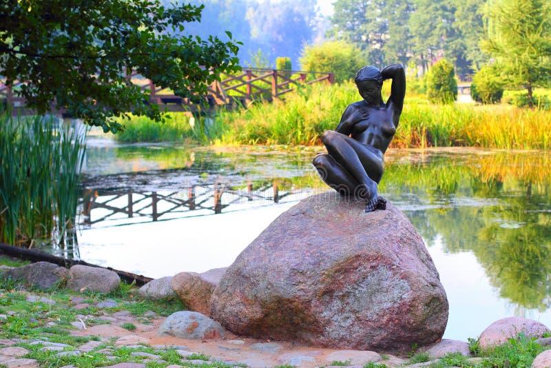 Skulpturbadegastmädchen, das auf einem Felsen sitzt lizenzfreie stockfotografie
