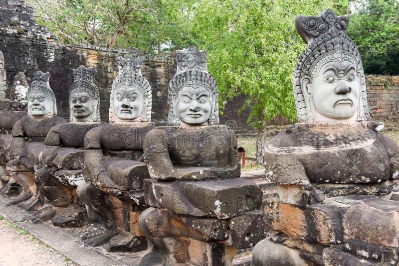 Skulpturer av demoner på den södra porten till Angkor Thom, Cambodja royaltyfria foton